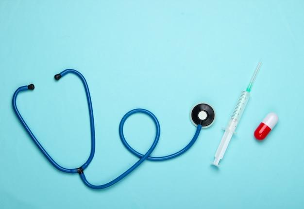 Composition de médecine plate laïque. capsule de pilule, stéthoscope, seringue avec vaccin sur fond bleu pastel. vue de dessus