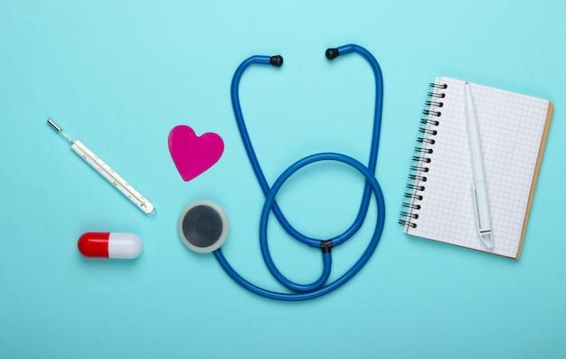 Composition de médecine plate laïque. capsule de pilule, thermomètre, stéthoscope, cahier sur fond bleu pastel. vue de dessus