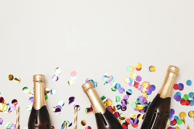 Composition avec mini bouteilles de champagne et paillettes sur espace blanc, espace copie