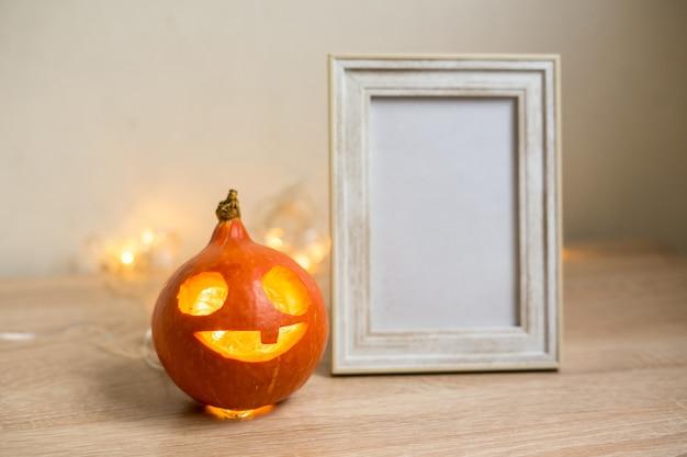 Composition minimale d'automne. concept de vacances de thanksgiving. cadre photo, citrouille sur fond blanc. vue de face, espace de copie. photo de haute qualité