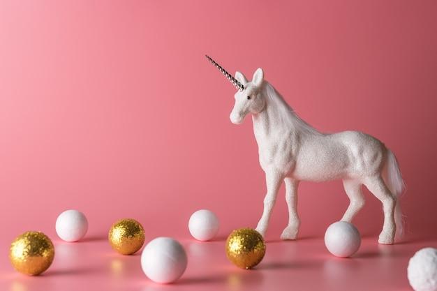 Composition minimale avec licorne scintillante et décoration blanche et or