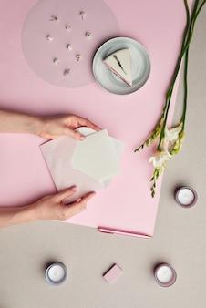 Composition minimale de mains féminines tenant une lettre dans une enveloppe sur fond graphique rose avec décor floral,