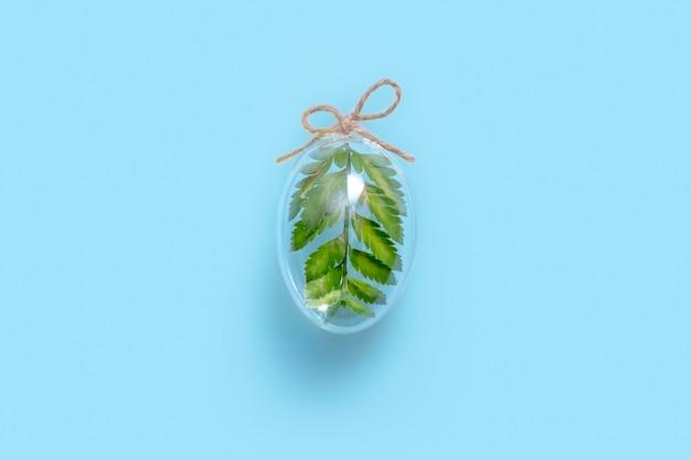 Composition minimale de pâques avec un œuf en verre transparent rempli de feuille de fougère verte sur fond bleu. concept de décor élégant eco.