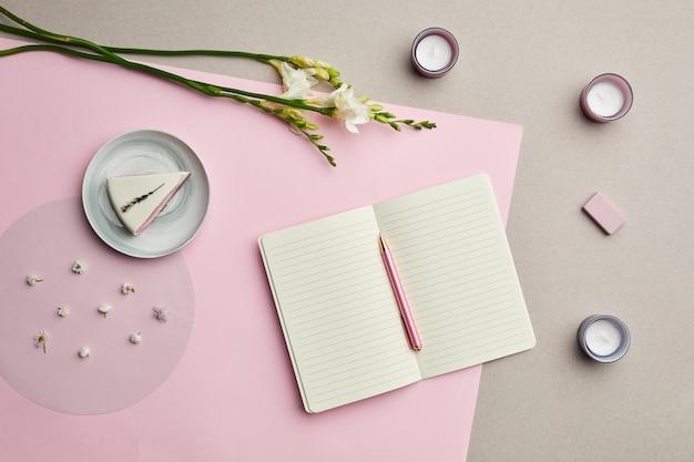 Composition minimale de planificateur vierge sur fond graphique rose avec décor floral,