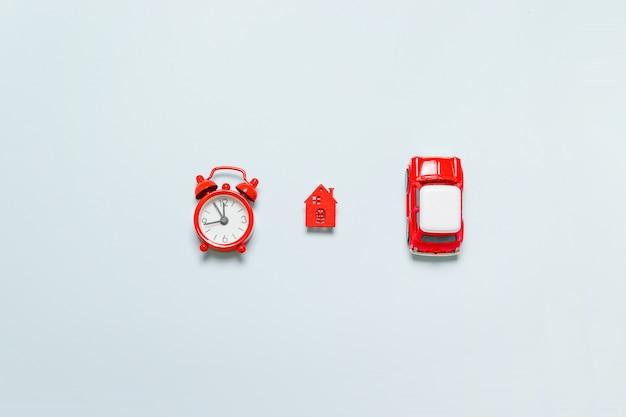 Composition minimale avec un réveil rouge, une petite voiture pour enfants et une maison.