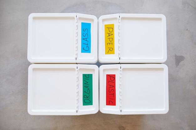 Composition minimale de la vue de dessus de quatre bacs en plastique étiquetés pour le stockage et le tri des déchets à la maison