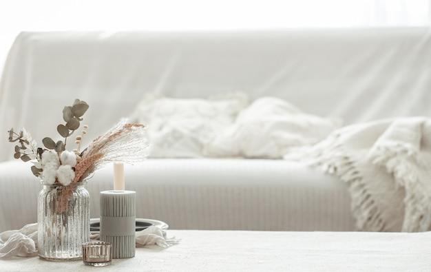 Une composition minimaliste dans le style scandinave avec des fleurs séchées dans un vase et des bougies.