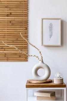 Composition minimaliste et design de fleurs séchées dans un vase élégant, une table basse en bois, une décoration, un cadre photo et des accessoires dans un intérieur blanc du salon.