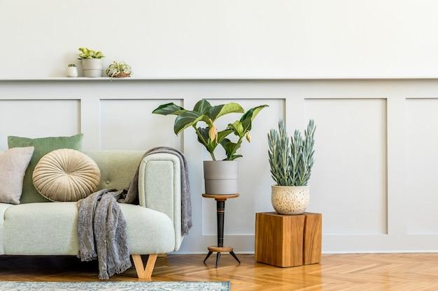Composition minimaliste du salon avec canapé design, plante, livres, décoration, oreillers, plaid, tapis, boiseries et accessoires élégants dans un décor élégant. espace de copie.