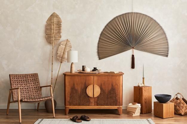 Composition minimaliste du salon avec commode en bois, lampe de table, fleur séchée dans un vase, livre, décoration et accessoires personnels élégants dans un décor élégant. modèle. espace de copie.
