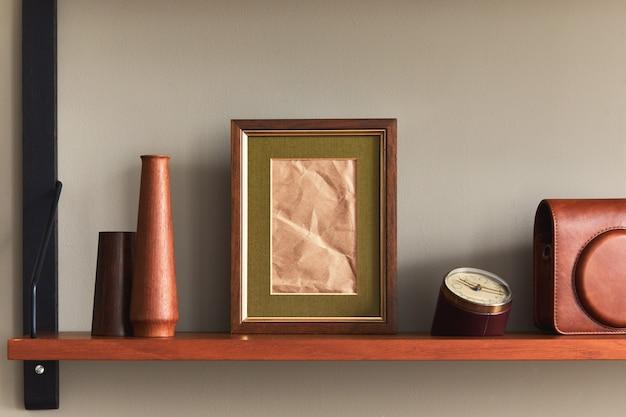 Composition minimaliste sur étagère en bois avec cadre photo marron, horloge, vase, étui pour appareil photo et accessoires personnels élégants dans un décor élégant.