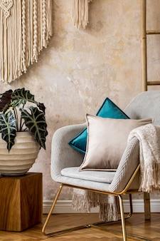 Composition minimaliste de l'intérieur du salon avec fauteuil design, table basse, échelle en bois, macramé, tapis et accessoires élégants dans une décoration moderne. mur de wabi sabi.