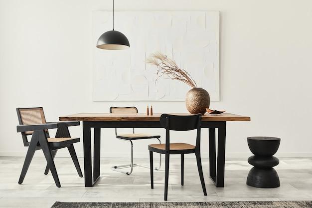 Composition minimaliste de l'intérieur de la salle à manger avec table en bois, chaises design, fleurs séchées dans un vase, suspension noire, peintures d'art au mur et accessoires personnels élégants