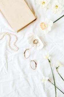 Composition minimaliste à la mode française avec accessoires pour femmes: boucles d'oreilles, collier, bagues sur lin blanc