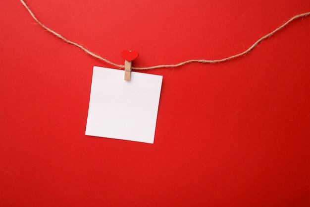 Composition minimaliste de la saint-valentin. note papier sur une pince à linge avec un cœur sur une corde. vue de dessus, maquette.