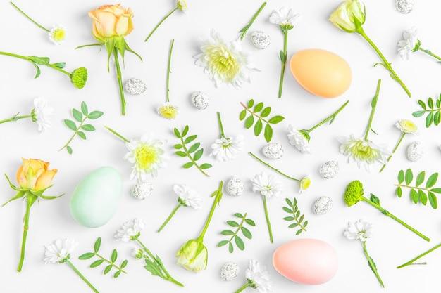 Composition de mise en page créative de fleurs et d'oeufs de pâques sur fond pastel.
