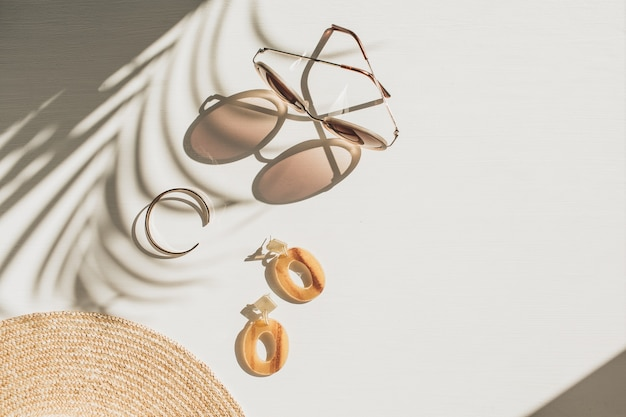 Composition de mode avec des accessoires pour femmes sur fond blanc. boucles d'oreilles, lunettes de soleil