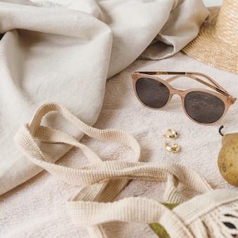 Composition de mode neutre avec accessoires pour femmes et bijouterie sur couverture beige. sac à cordes, chapeau de paille, lunettes de soleil, bagues, boucles d'oreilles, poire
