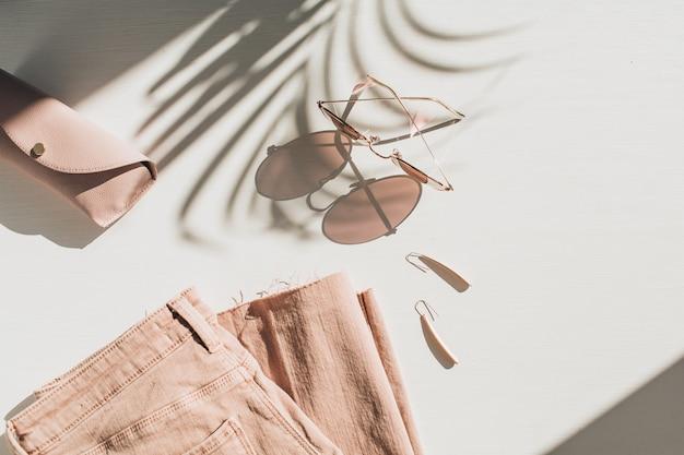 Composition de mode avec des vêtements et accessoires pour femmes sur blanc. boucles d'oreilles, lunettes de soleil, jupe-culotte en jean rose sur blanc