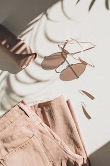 Composition de mode avec des vêtements et accessoires pour femmes sur fond blanc. boucles d'oreilles, lunettes de soleil, jupe-culotte en jean rose sur fond blanc.