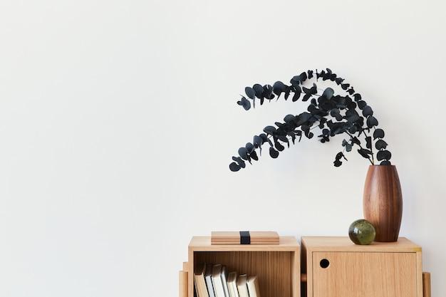Composition moderne de l'intérieur du salon avec bibliothèque en bois design, feuille d'eucalyptus dans un vase, livre, décoration, boule vitreuse et espace de copie sur le mur blanc