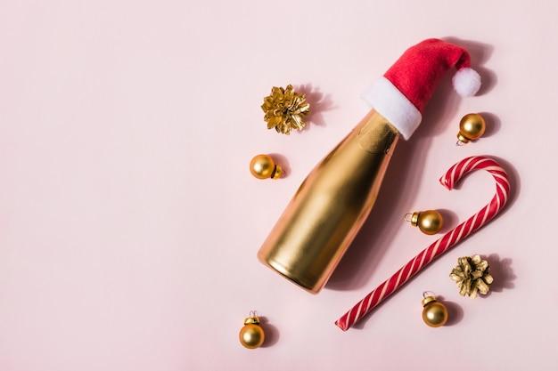 Composition moderne de noël faite de champagne d'or dans la canne et les jouets de bonbon de santa hat