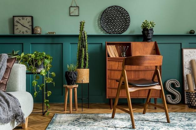 Composition moderne et rétro de l'intérieur du bureau à domicile avec armoire en bois, chaise, plantes, décoration et accessoires personnels élégants. concept vintage élégant de décoration intérieure. lambris en bois. modèle.