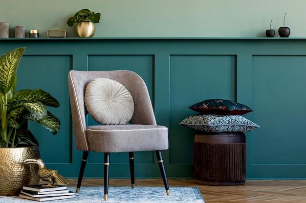 Composition moderne de salon avec fauteuil design gris, pot doré avec belle plante, pouf, coussins et accessoires personnels élégants. lambris mural avec étagère. home staging élégant..