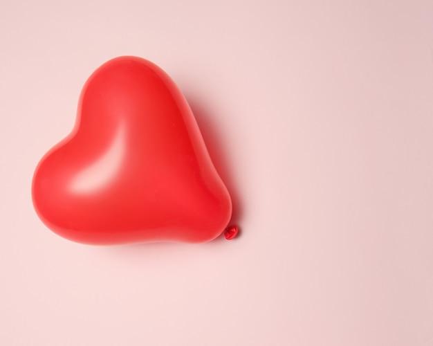 Une composition avec une montgolfière en forme de coeur sur fond rose.