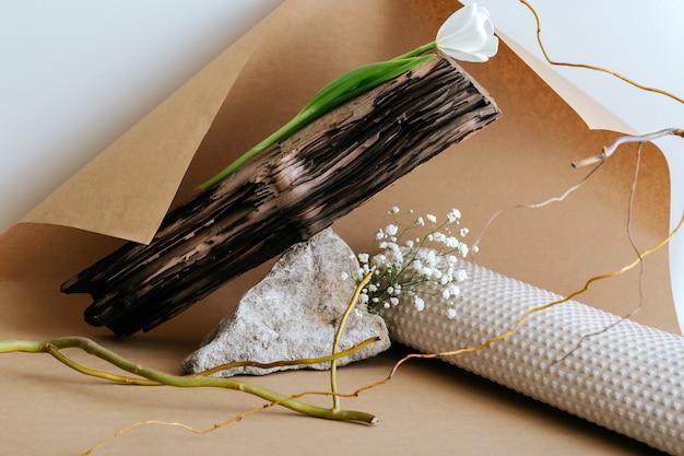 Composition de nature morte boho monochrome minimaliste abstraite créative avec des matériaux naturels en pierre bois papier fleur plante branches sèches sur fond de papier kraft brun.