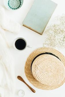 Composition de nature morte avec café, livre, fleurs, chapeau de paille et couverture sur une surface blanche
