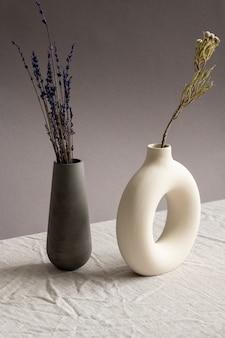 Composition de nature morte avec deux vases faits à la main en céramique avec lavande séchée et fleurs sauvages debout sur une table recouverte de toile de lin blanc
