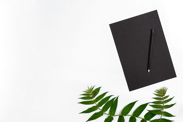 Composition naturelle avec carnet de croquis et crayons sur table blanche décorée de branches vertes à plat...