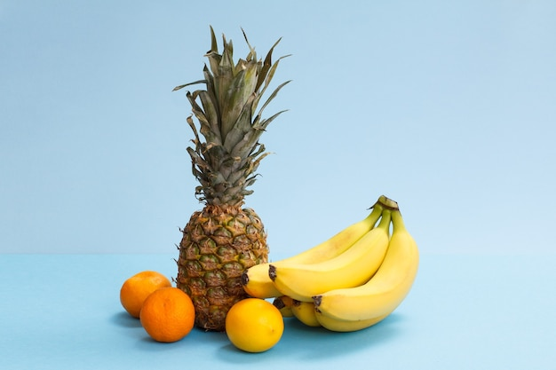Composition naturelle de fruits tropicaux. ananas frais, bananes, citron et oranges sur fond bleu.