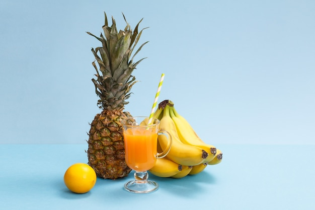 Composition naturelle de fruits tropicaux. ananas frais, bananes et citron avec verre de jus de fruits sur fond bleu.