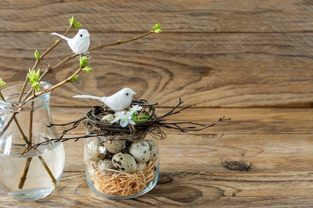 Composition avec nid de brindilles, œufs de caille et petits oiseaux. vacances de pâques dans un style rustique.