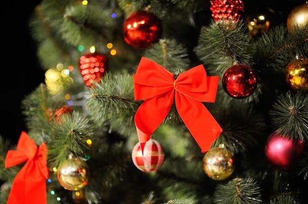 Composition de noël avec arbre de noël, décorations de noël et un grand arc rouge