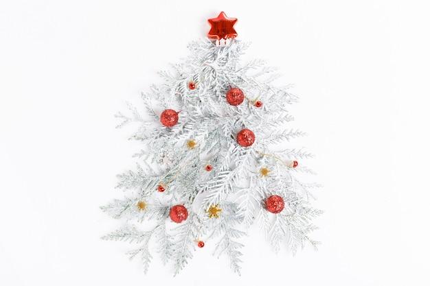 Composition de noël. arbre de noël fait de branches de conifères, boules rouges, décorations dorées sur fond blanc.