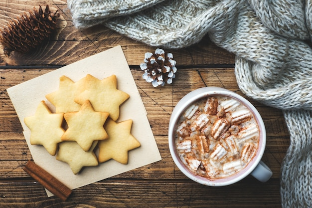 Composition de noël, biscuits au chocolat chaud, branches de pin, bâtons de cannelle, étoiles d'anis.