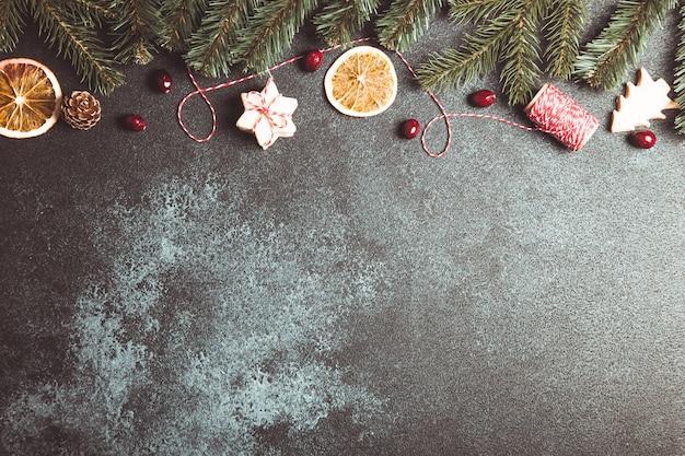Composition de noël avec des biscuits, des branches d'arbres de noël et des oranges séchées.