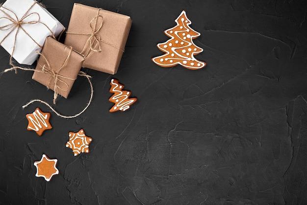 Composition de noël biscuits de noël cadeaux décoration festive sur fond noir vue de dessus à plat avec ...