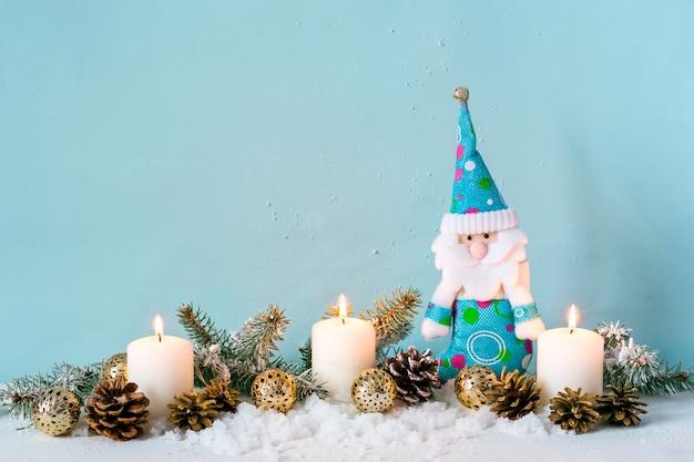 Composition de noël bleu. bougies et nain parmi les branches de sapin