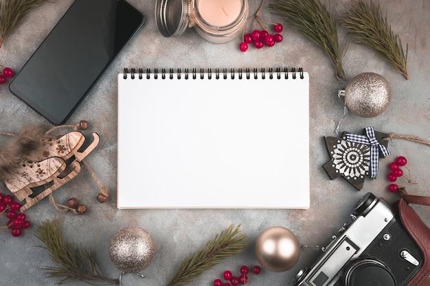 Composition de noël de bloc-notes, branches de pin, café, téléphone et appareil photo rétro sur une surface grise
