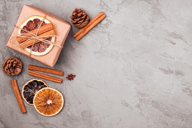 Composition de noël boîte-cadeau cannelle anis fruits secs et décorations de pommes de pin sur fond gris