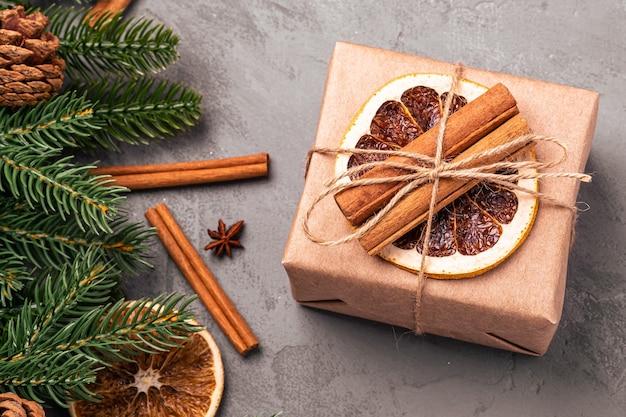 Composition de noël boîte-cadeau cannelle anis fruits secs pommes de pin et aiguilles de sapin décorations sur gris