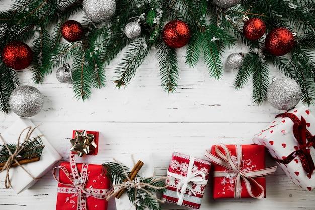 Composition de noël de boîtes-cadeaux rouges et de branches de sapin