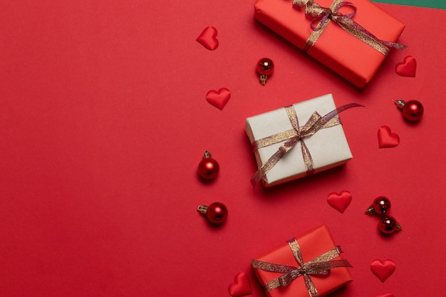 Composition de noël de boîtes surprise décorées de rubans brillants, boules de noël rouges, formes de coeur sur fond rouge