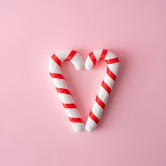 Composition de noël. bonbons de noël sur mur rose. joyeuses fêtes.