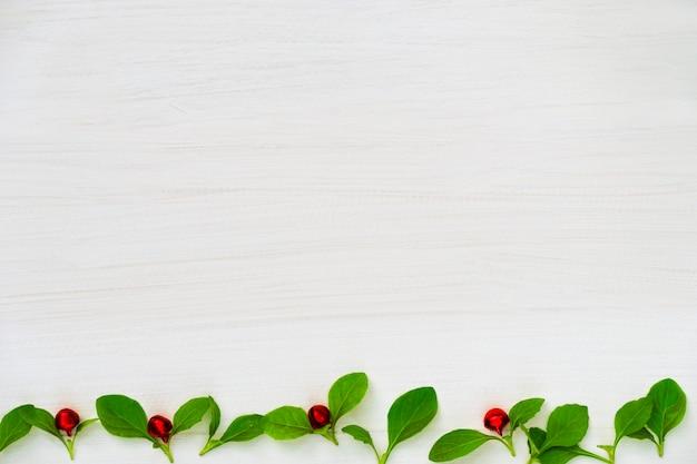 Composition de noël et bonne année. feuille verte et boule rouge sur fond blanc.