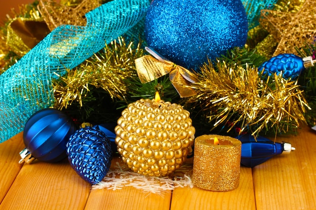Composition de noël avec des bougies et des décorations aux couleurs bleu et or sur fond de bois